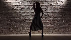 Menina em twerk listrado da dança do vestido contra a parede de tijolo leve Silhueta Movimento lento video estoque