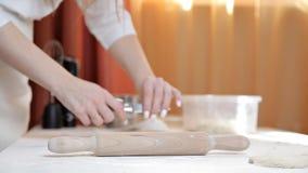 Menina em um avental que prepara a massa crua da pizza A menina está preparando uma pizza deliciosa em casa pastry filme
