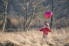 Menina em um balão coração-dado forma terra arrendada do campo Imagem de Stock