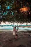 Menina em um balanço na praia do malheureux do tampão, Maurícias foto de stock