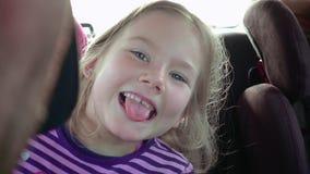A menina em um banco de carro da criança sorri e ri vídeos de arquivo