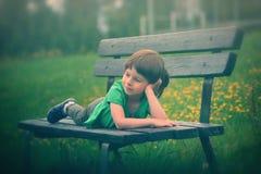 Menina em um banco de madeira imagens de stock