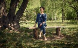 Menina em um banco de madeira na natureza da floresta, parque verão em Ucrânia Imagens de Stock