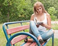 Menina em um banco de parque que lê um livro Fotos de Stock