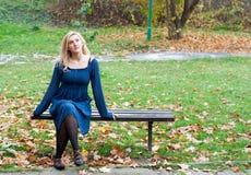 Menina em um banco no parque Fotos de Stock