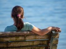 Menina em um banco pelo mar imagens de stock royalty free