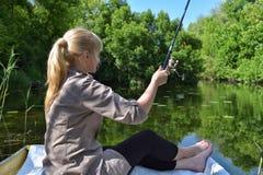 A menina em um barco está pescando no lago Imagem de Stock Royalty Free