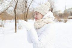 A menina em um branco do inverno para baixo-acolchoou o revestimento Imagem de Stock