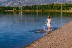 A menina em um branco molhou o vestido que corre ao longo do lago fotografia de stock royalty free