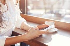 menina em um café com um telefone e uma xícara de café Imagem de Stock