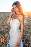 Menina em um campo branco do vestido, felicidade do sorriso do trigo, brilho bonito do cabelo do sol Foto de Stock Royalty Free