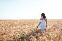 Menina em um campo branco do vestido, recreação exterior do trigo, vestido bonito Passeio no campo no verão Fotos de Stock Royalty Free