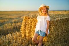 Menina em um campo com rolos do feno Imagens de Stock Royalty Free