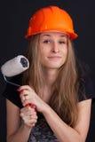 Menina em um capacete com um rolo em sua mão Fotos de Stock Royalty Free