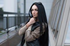 Menina em um casaco de cabedal que está perto da construção fotografia de stock