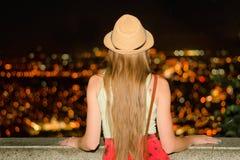 A menina em um chapéu admira a cidade da noite Vista traseira fotografia de stock