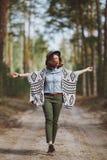 A menina em um chapéu anda através das madeiras do outono Fotografia de Stock Royalty Free