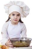 A menina em um chapéu branco do avental e dos cozinheiros chefe amassa a massa no th Fotos de Stock