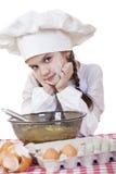 A menina em um chapéu branco do avental e dos cozinheiros chefe amassa a massa no th Fotos de Stock Royalty Free
