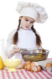 A menina em um chapéu branco do avental e dos cozinheiros chefe amassa a massa no th Fotografia de Stock