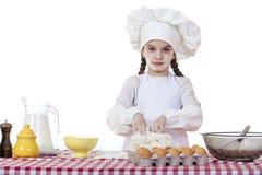 A menina em um chapéu branco do avental e dos cozinheiros chefe amassa a massa no th Fotografia de Stock Royalty Free