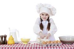 A menina em um chapéu branco do avental e dos cozinheiros chefe amassa a massa no th Imagens de Stock