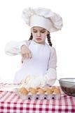A menina em um chapéu branco do avental e dos cozinheiros chefe amassa a massa no th Imagem de Stock