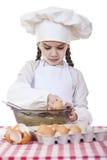 A menina em um chapéu branco do avental e dos cozinheiros chefe amassa a massa no th Foto de Stock