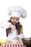 A menina em um chapéu branco do avental e dos cozinheiros chefe amassa a massa no th Imagem de Stock Royalty Free