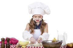 A menina em um chapéu branco do avental e dos cozinheiros chefe amassa a massa no th Foto de Stock Royalty Free