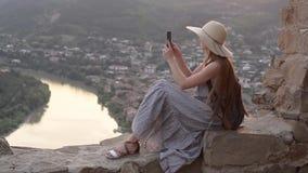 Menina em um chapéu com uma trouxa que senta-se no monte Dispara no vídeo ao smartphone, cidade abaixo video estoque