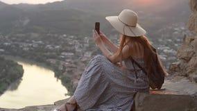 Menina em um chapéu com uma trouxa que senta-se no monte Dispara no vídeo ao smartphone, cidade abaixo filme