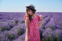 A menina em um chapéu de palha olha em torno dela foto de stock royalty free