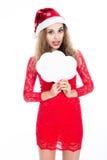 Menina em um chapéu do Natal que guarda bandeiras sob a forma das nuvens Fotos de Stock