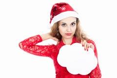 Menina em um chapéu do Natal que guarda bandeiras sob a forma das nuvens Foto de Stock