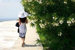 A menina em um chapéu e em um vestido brancos do branco vai Imagens de Stock