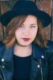 A menina em um chapéu está sobre um fundo de madeira fotos de stock royalty free