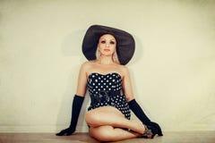 Menina em um chapéu largo-brimmed que olha acima Imagens de Stock Royalty Free
