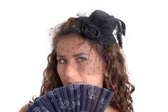 Menina em um chapéu negro com um fã fotografia de stock