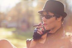 A menina em um chapéu negro fuma um charuto Imagens de Stock Royalty Free