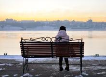 Menina em um chapéu que senta-se em um banco no passeio de volta ao Ca Foto de Stock Royalty Free