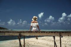 Menina em um chapéu que senta-se em uma ponte de madeira maldives Areia branca Foto de Stock Royalty Free