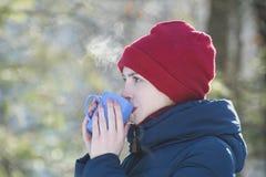 Menina em um chapéu vermelho e em uma caneca em sua posição da mão na perspectiva das hortaliças Retrato Close-up fotos de stock