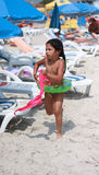 A menina em um disco inflável funciona na praia Imagem de Stock Royalty Free
