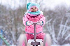 A menina em um fato-macaco cor-de-rosa anda em um parque nevado do inverno imagens de stock