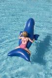 Menina em um golfinho plástico Fotografia de Stock