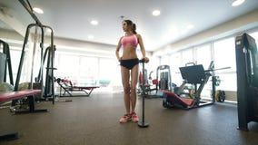Menina em um gym que levanta oposto a um espelho filme