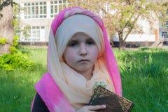 A menina em um lenço Estudo da Bíblia no ar fresco fotos de stock
