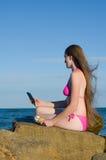 Menina em um maiô nas rochas na praia com um gelado e um smartphone nas mãos Fotos de Stock Royalty Free