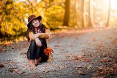 Menina em um parque com as folhas de outono em torno dela foto de stock royalty free